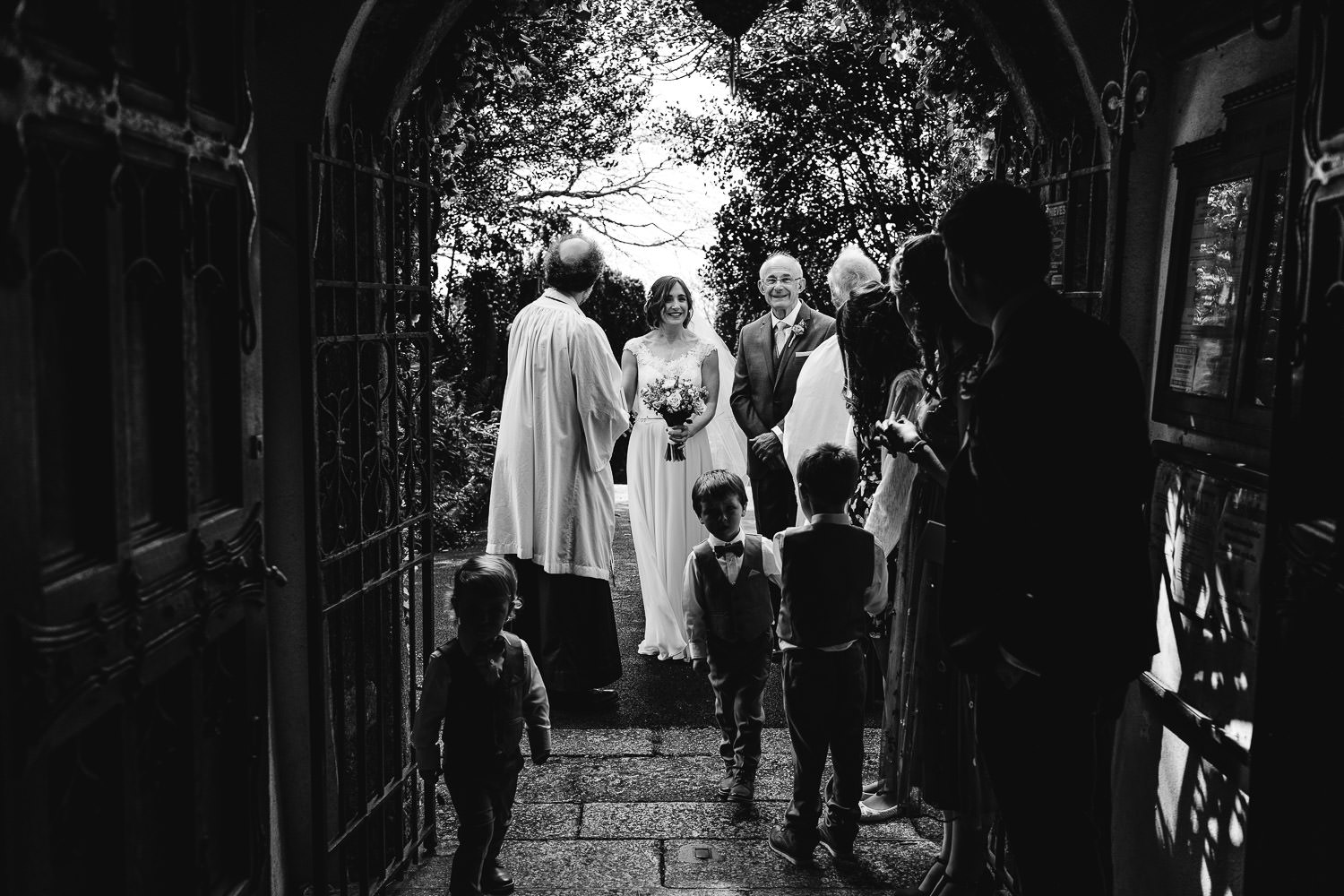 bride, bridesmaids, dad and page boys wait outside Gulval church with the Vicar