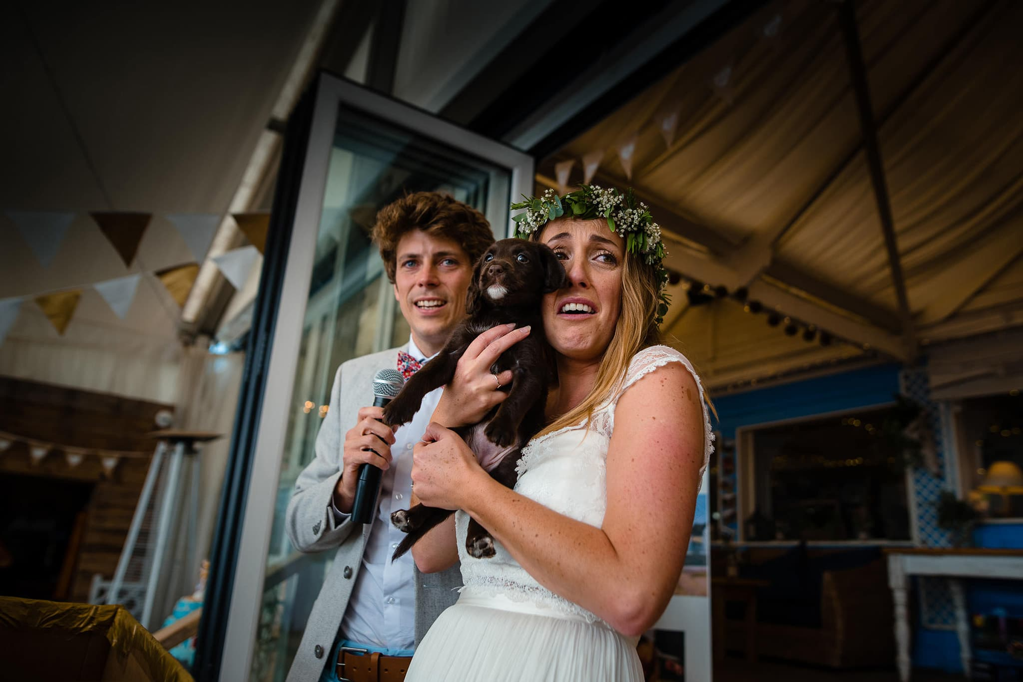 Bride and groom with puppy at Lusty Glaze wedding